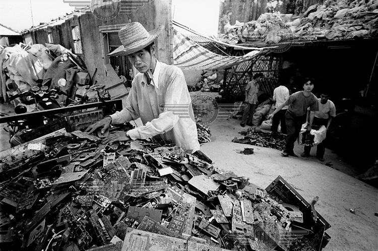 A man sorts through a large pile of circuitry. Every year Guiyu takes in more than a million tons of computer waste, imported from all over the world. About 40,000 local farmers and 100,000 migrant workers make their living from the e-waste, which contains toxic ingredients such as lead, beryllium and mercury. The workers risk catching respiratory and skin diseases, eye infections and even cancer..