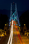 Cars (and a bicyclist on the left) cross the Lions Gate Bridge from Stanley Park in Vancouver, British Columbia to North Vancouver at night.