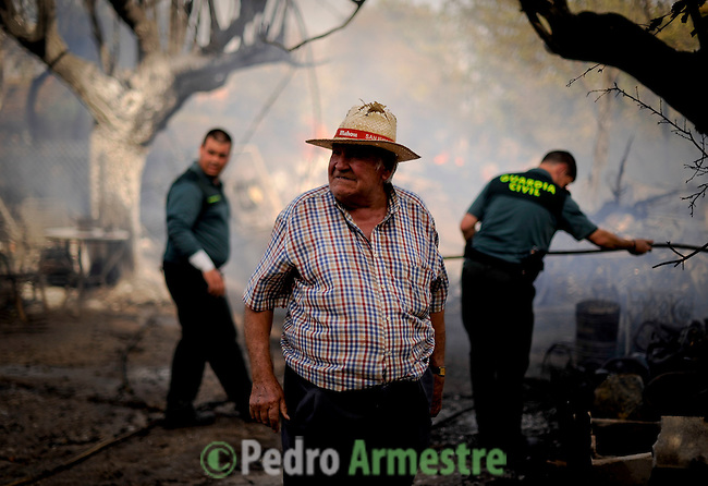 A neighbour stands in San Agustin de Guadalix during a forest fire near Madrid, on August 11, 2012. Wildfires raged Saturday in Spain's Canary Islands and in mainland Galicia, as hundreds fought a blaze near Mount Athos in Greece, a UN Heritage Site housing the world's oldest monastic community. (c) Pedro ARMESTRE