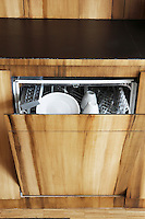 A dishwasher is concealed behind a cupboard door painted in a wood grain effect
