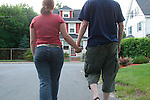 teenage boy and girl walking holding hands in suburban neighborhood, young love