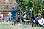 Festival crew member keeps monkeys away from the fruit until the Festival begins using a sling shot