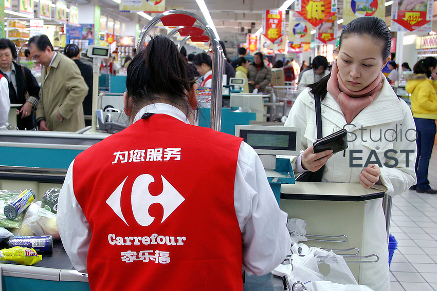 "A cashier counts a customer's purchases in Carrefour supermarket in Shanghai, China, on March 24, 2005. Some Chinese Internet users have launched a boycott of French products, in order to protest against the way the Olympic torch was handled when in Paris. A short text message is circulating between Chinese users, saying ""Let's not buy anything at Carrefour's. Let's boycott Carrefour at least until the Olympics"". Photo by Eric Leleu/Pictobank"