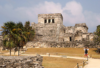 Tourist photographing El Castillo at the Mayan ruins of Tulum on the Riviera Maya, Quintana Roo, Mexico.