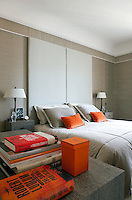 A giant headboard in the master bedroom is covered in a tranquil pale grey fabric by Hermes