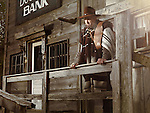 Cowboy with a cigar in his mouth standing in outside of a bank building