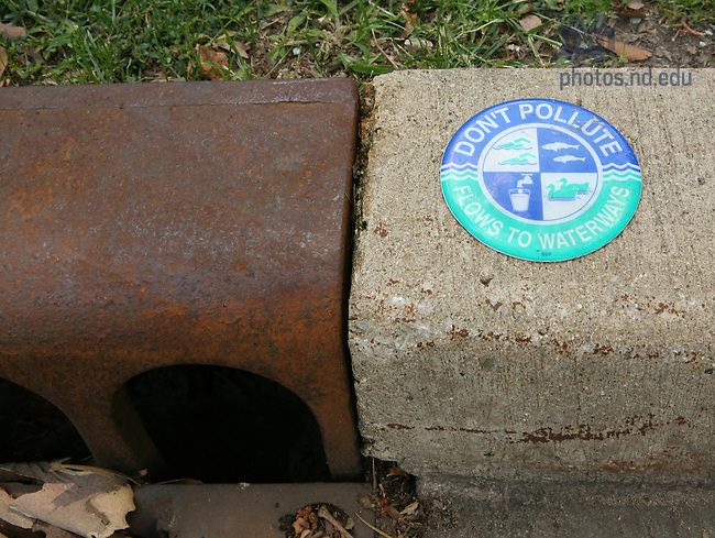 """Signs next to storm drains say """"Don't pollute, flows to waterways."""".For Notre Dame Magazine"""