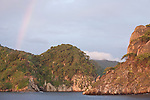 Cocos Island, Costa Rica; a rainbow over Cocos Island at sunrise after a tropical rainshower passed through