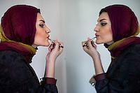Model, Sahar, applying make-up before a photo shoot.