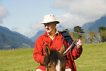 Chile, Lake Country: People riding horses at Peulla in a meadow in the Andes..Photo #: ch615-33260..Photo copyright Lee Foster www.fostertravel.com, lee@fostertravel.com, 510-549-2202.