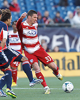 FC Dallas forward Kenny Cooper (33) takes a shot..  In a Major League Soccer (MLS) match, FC Dallas (red) defeated the New England Revolution (blue), 1-0, at Gillette Stadium on March 30, 2013.