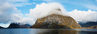 Cloud covered Olstinden mountain peak rises from Kjerkfjord, Reine, lofoten Islands, Norway
