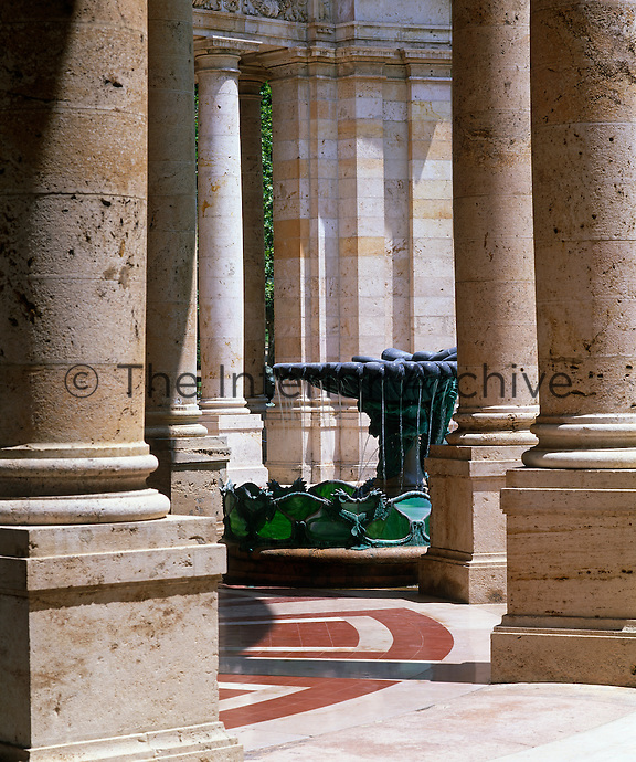 A fountain decorated with green glass glimpsed through a series of columns