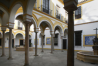 Low angle view of the double patio, Hospital de la Caridad (Charity Hospital), Seville, Spain, pictured on January 3, 2007, in the afternoon. Founded in 1674 by Miguel de Manara, the Hospital de la Caridad is a refuge for poor and elderly people. An outstanding example of Sevillian Baroque with whitewashed walls and terracotta stonework, it was designed by Pedro Sanchez Falconete. The buildings stand around a double patio divided by arches. Picture by Manuel Cohen.
