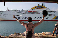 "A migrant from Yemen waves to a passenger ship en route to Italy, and shouts ""No room for one more?!"". Patras, Greece."