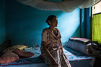 India – West Bengal: Mina Sharma, 45, posing inside her house at Mogulkata Tea Estate, in the Dooars region. The woman started working as a plucker when she was 30, after taking over her mother's job. Once she will retire, she hopes her 25-year-old married daughter will take her position, otherwise Sharma would lose her house and plot of land which, like all the other properties within the tea estate, belong to the company. With no money to buy another dwelling, the woman has no other option but to keep on living here.