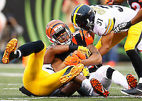 Marvin Jones #82 of the Cincinnati Bengals is tackled following a catch by Mike Mitchell #23 and Ross Cockrell #31 of the Pittsburgh Steelers during the game at Paul Brown Stadium on December 12, 2015 in Cincinnati, Ohio. (Photo by Jared Wickerham/DKPittsburghSports)