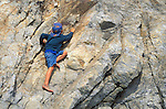 Barefoot boy climbing on rock at Sand Dollar Beach on the Big Sur Coast, Los Padres National Forest, California USA