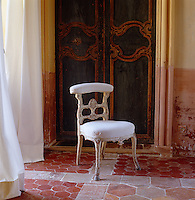 A chair in front of the panelled double doors of the bedroom