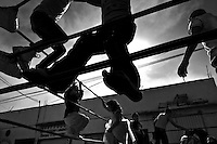"""Mexican kids play on the ropes of the ring before a fight at a local arena in Mexico City, Mexico, 28 May 2011. Lucha libre, literally """"free fight"""" in Spanish, is a unique Mexican sporting event and cultural phenomenon. Based on aerial acrobatics, rapid holds and the use of mysterious masks, Lucha libre features the wrestlers as fictional characters (Good vs. Evil). Women wrestlers, known as luchadoras, often wear bright shiny leotards, black pantyhose or other provocative costumes. Given the popularity of Lucha libre in Mexico, many wrestlers have reached the cult status, showing up in movies or TV shows. However, almost all female fighters are amateur part-time wrestlers or housewives. Passing through the dirty remote areas in the peripheries, listening to the obscene screams from the mainly male audience, these no-name luchadoras fight straight on the street and charge about 10 US dollars for a show. Still, most of the young luchadoras train hard and wrestle virtually anywhere dreaming to escape from the poverty and to become a star worshipped by the modern Mexican society."""