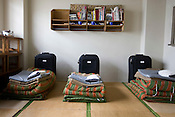 In a room shared by seven prisoners, the folded futon and bedding for three of them sits neatly beside black cases in which they can store their personal belongings during the day in Onomichi prison, Japan. Monday, May 19th, 2008