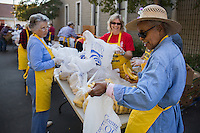 Volunteers prepare bags of bananas that will be distributed along with other produce. In Sanger, CA, needy families arrive in the middle of the night to wait in line for food distribution the next day. Many sleep in their cars after placing carts and boxes out as place holders. Drought conditions have led to job loss and food insecurity in this, one of America's most important agricultural regions.