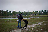 Jacksonville, Florida<br /> November 5, 2013<br /> <br /> Veteran's sustainable farm founded by Purple Heart veteran Adam Burke and managed by Afghan and Iraqi veteran Steve Ellseberry.<br /> <br /> The land ower's dog (Dex) appears to be dancing with army veteran Steve Ellseberry as he passes the farm's irrigation pond on the way to the goat pen.