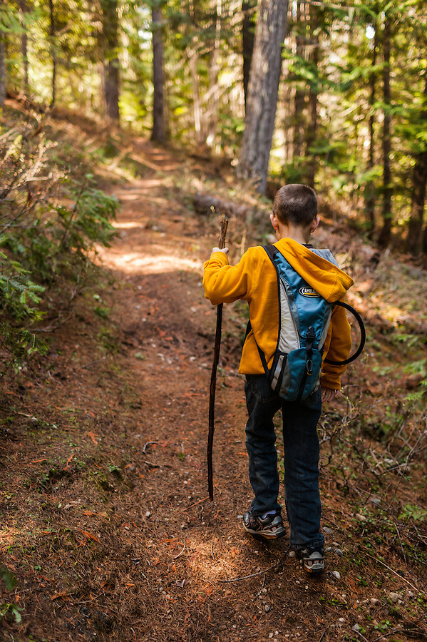 An active 7 year old boy carries a hiking stick as he travels through North Idaho on a trail near Priest Lake in Bonner County.