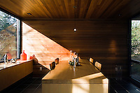 A bespoke maple table in the dining area is enveloped in cedar wood panelling on walls and ceiling