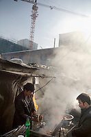 A Uighur barbecue stand operates underneath new construction in the Uighur section of Urumqi, Xinjiang, China. The city is divided between Han and Uighur ethnic groups and in 2009 saw violent clashes between the groups.