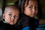 A young girl carries her baby brother on her back in rural Laos, near Luang Prabang. Older children are often responsible for their younger siblings.