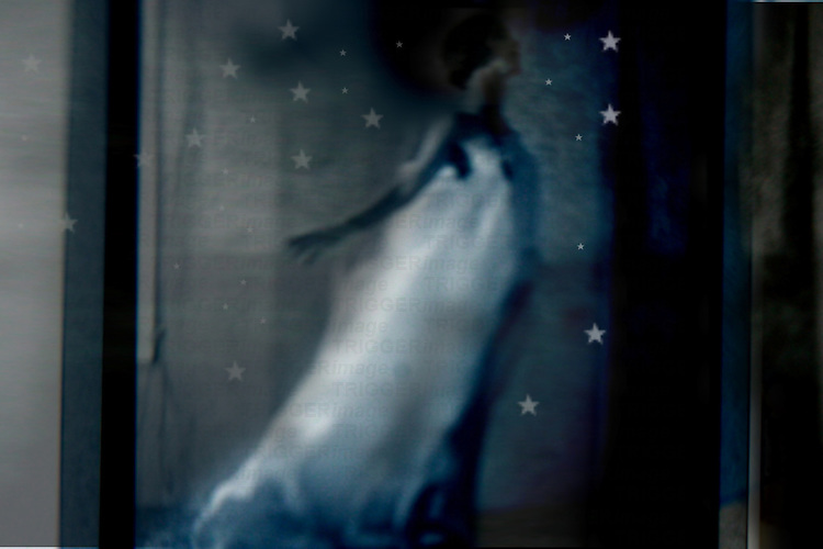 A blurred image of a woman and stars wearing a white dress in profile