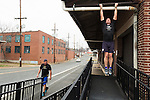December 22, 2014. Lexington, North Carolina.<br />  Mayor Newell Clark does chin-ups at an old railroad depot as part of his exercise routine, while his cousin Stan Lanier looks on.<br />   Newell Clark, the 43 year old mayor of Lexington, NC, leads a group of friends and colleagues on a 4 times a week exercise routine around downtown. The group uses existing infrastructure, such as an abandoned furniture factory, loading docks, stairs, and handrails to get fit and increase awareness of healthy lifestyles in a town more known for BBQ.<br /> Jeremy M. Lange for the Wall Street Journal<br /> Workout_Clark