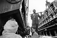 India. Province of Gujarat. Alang. Workers, all men, dismantle the engine of a freighter boat. Alang, located in the Gulf of Khambhat, is a ships breaking place and is considered as the biggest scrapyard in the world. Ships recycling for its metals. Environmental issues. Hazardous waste. © 1992 Didier Ruef