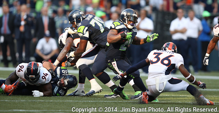 Seattle Seahawks running back Marshawn Lynch (24) looks for running room against  Denver Broncos cornerback Kayvon Webster (36)  in overtime at CenturyLink Field in Seattle, Washington on September 21, 2014.   Lynch ran for 88 yards and scored two touchdowns in the Seahawks 26-20 overtime win over the Broncos.  Providing blocking against the Broncos defenders is tackle Russell Okung (76)  and tight end Zach Miller (86)  ©2014. Jim Bryant Photo. All rights Reserved.