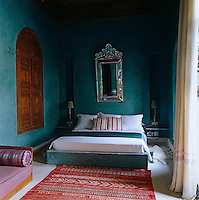 One of six bedrooms in the riad, the low concrete bed frame has been painted the same blue/green as the walls