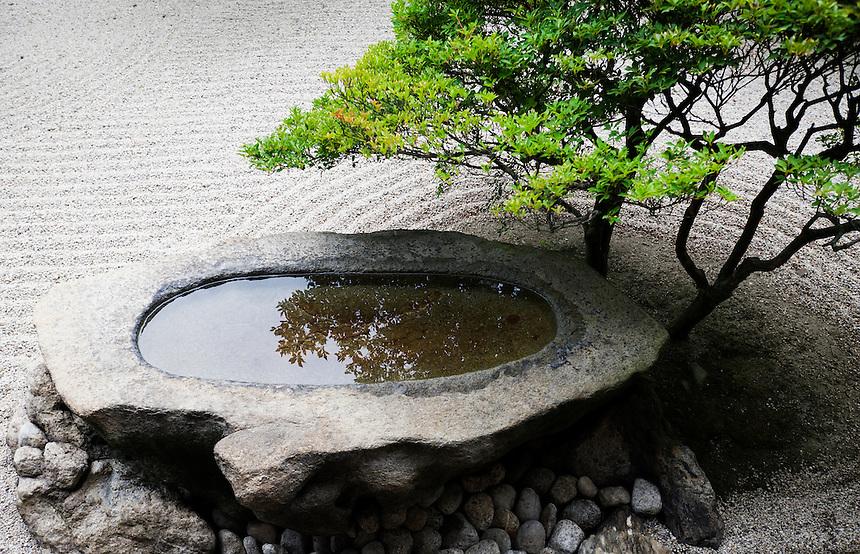 A stone basin reflects a beautifully manicured shrub at a karesansui (dry landscape) garden in Ritsurin Koen, Takamatsu.
