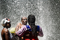 A Haitian man seen in trance under the waterfall, supposedly possessed by a Voodoo spirit, during the annual religious pilgrimage in Saut d'Eau, Haiti, July 16, 2008. Every year in summer thousands of pilgrims from all over Haiti make the religious journey to the Saut d'Eau waterfall (100km north of Port-au-Prince). It is believed that 150 years ago the spirit of Virgin Mary (Our Lady of Mount Carmel) has appeared on a palm tree close to the waterfall. This place became a main pilgrimage site in Haiti since then. Haitians wearing only underwear perform a bathing and cleaning ritual under the 100-foot-high waterfall. Voodoo followers (many Haitians practise both voodoo and catholicism) hope that Erzulie Dantor, the Voodoo spirit of water, manifest itself and they get possessed for a short moment, touched by her presence.