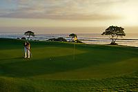 Lone golfer putting on seaside green, Kauai, Hawaii