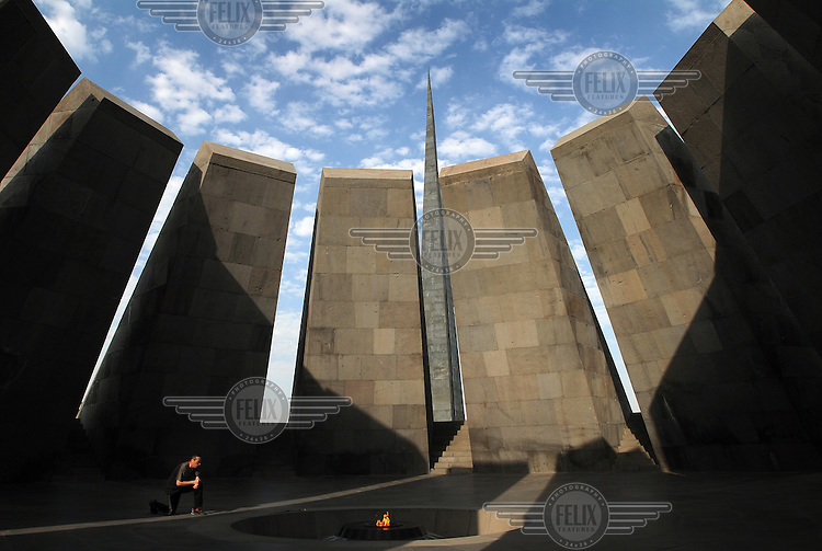A man kneeling before the Tsitsernakaberd memorial, dedicated to the 1915 Armenian Genocide, on a hill overlooking Yerevan. Made up of 12 basalt slabs leaning inward over an eternal flame, the memorial symbolizes the rebirth of the Armenian nation.