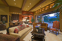 Colorful family room with beamed ceiling and clerestory windows features sliding glass wall that open to outside