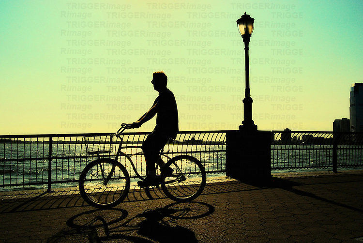 A man riding a bike in solitude on the Promenade, Battery Park, New York City