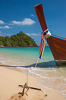 Long tail boat with colorful scarves honoring the goddess of travel anchored on a tropical beach in the Andaman Sea near Koh Lanta Thailand