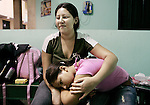 Sharon Reyes, 18, holds her sister, Marjorie, 10, in women's sitting area of Casa del Migrante, on Tuesday, May 8, 2007, in Tecun Uman, Guatemala. They long to reunite with their mother who is working in Los Angeles. However, their fear of crossing the river, the dangers of crossing Mexcio and lack of money to continue the journey crushed their hope of being their mother. They await a call from a cousin who said he can get them a ride across the border. They would have to hide in the car from border officials.