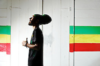 Cali P, the lyrical fayah silhouette with rasta color wall