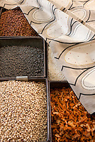 Metal boxes are used to display a variety of spices on this market stall