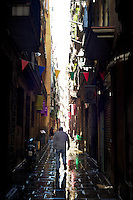 a man walks by him self in old barcelona streets and alleys, colored flags over his head
