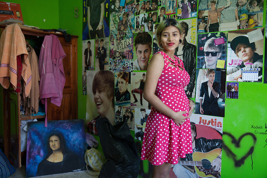 Xochiquetzal S&aacute;nchez Escobar portrayed in her bedroom at her home in Juchit&aacute;n, Mexico on February 18, 2016. Despite her teenage rebel style, Xochi, as she is known, dressed in the traditional Zapotec style for her engagement party. She is 17 and five months pregnant. The daughter of a single-mother former missionary and nun, Xochi says she had always talked about having a baby in her teens because she thought her mother was old when she had her at 28. She kept her pregnancy secret from her mother until February. After the baby - a boy, David Mateo - is born in June, she plans to move with her boyfriend to a house where they will live together and he will have his tattoo studio, and they plan to marry next June. She plans to finish her final year of secondary school in the town of El Espinal in the southern Mexican state of Oaxaca next year, with her mother looking after the baby in the mornings while she is in class. Being a schoolgirl housewife does not worry her, she says, although she admits she cannot cook. Her grandmother, who lives with the family, is thrilled at the prospect of a great-grandchild. Xochi dreams of giving birth in water, but is not sure that will happen. While Mexico has outlawed marriage under the age of 18, many young girls become unofficial wives and mothers much earlier. In Juchit&aacute;n, teenage pregnancy is expected, even prized. Mexico ranks first in teenage pregnancies among the member countries of the Organization for Economic Co-operation and Development&nbsp;(OECD). Photo by B&eacute;n&eacute;dicte Desrus<br /> &nbsp;<br /> &nbsp;<br /> <br /> &nbsp;