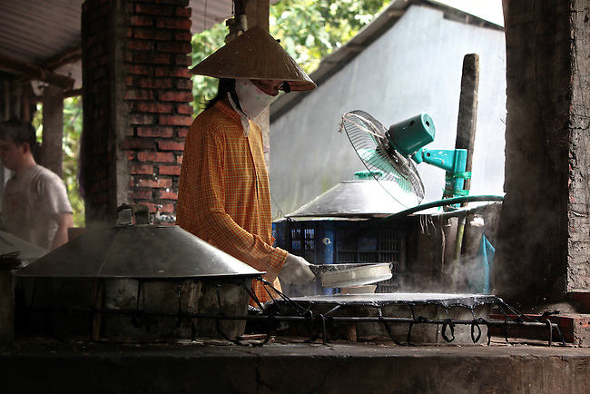 A woman makes rice noodle sheets at a small factory in the Mekong Delta, south of Can Tho, Vietnam. Sept. 30, 2011.