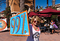 """Charlie proudly holds a """"99%"""" sign while marching to the Bank of America branch in Irvine CA; behind her a family of three looks on.  At the Occupy Orange County, Irvine march on November 5."""